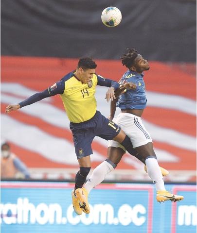 QUITO (Ecuador): Xavier Arreaga (L) of Ecuador and Colombia's Duvan Zapata jump for a header during their World Cup qualifier.—AP