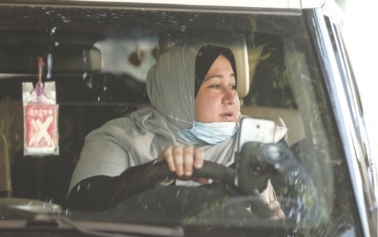 NAYLA Abu Jubbah, the first female Palestinian taxi driver in Gaza Strip, sits in her vehicle as she works in Gaza City.—AFP