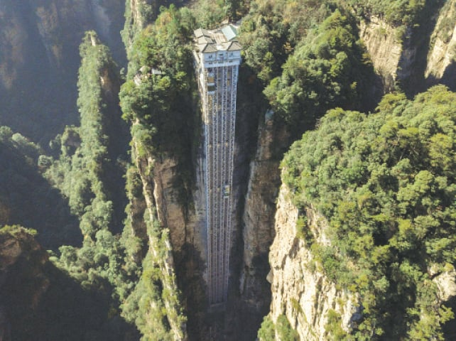 ZHANGJIAJIE (China): An aerial view of elevators that dare tourists to take a literally cliff-hanger of a ride to the top of a towering peak in China's Hunan province. The world's highest outdoor lift rewards brave tourists with breathtaking views of a majestic cliff that inspired the landscape for the blockbuster movie, Avatar.—AFP