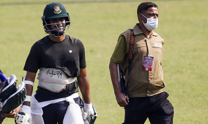 A security personnel (R) escorts cricketer Shakib Al Hasan as he leaves the field after a practice session at the Sher-e-Bangla National Cricket Stadium in Dhaka on November 18. — AFP