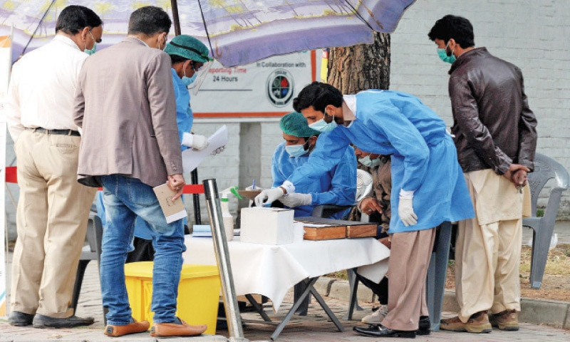 People gather around a mobile Covid-19 testing unit in F-6 to give samples on Thursday. Islamabad has witnessed a sharp increase in positive cases in recent days. — Photo by Mohammad Asim