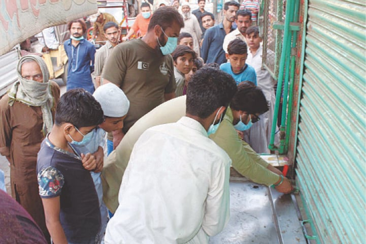 HYDERABAD: Government officials seal a shop in the city's cloth market on Thursday after its owner was caught violating SOPs for Covid-19 during an operation carried out by the local government.—PPI