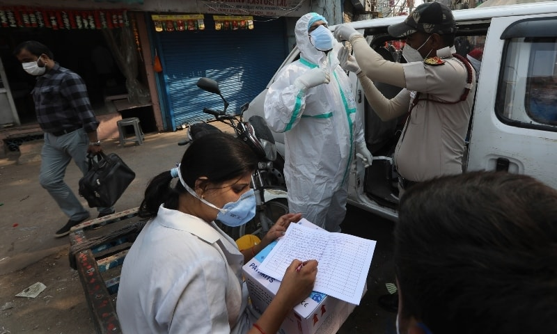 A health worker sitting on a hand cart registers people to test for Covid-19 t a market place in New Delhi on Nov 19. — AP