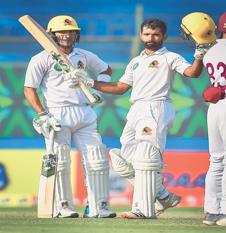 KARACHI: Sindh captain Asad Shafiq, watched by fellow century-maker Omair Bin Yousuf, celebrates reaching the three-figure mark against Southern Punjab at the National Stadium on Friday.—Courtesy PCB