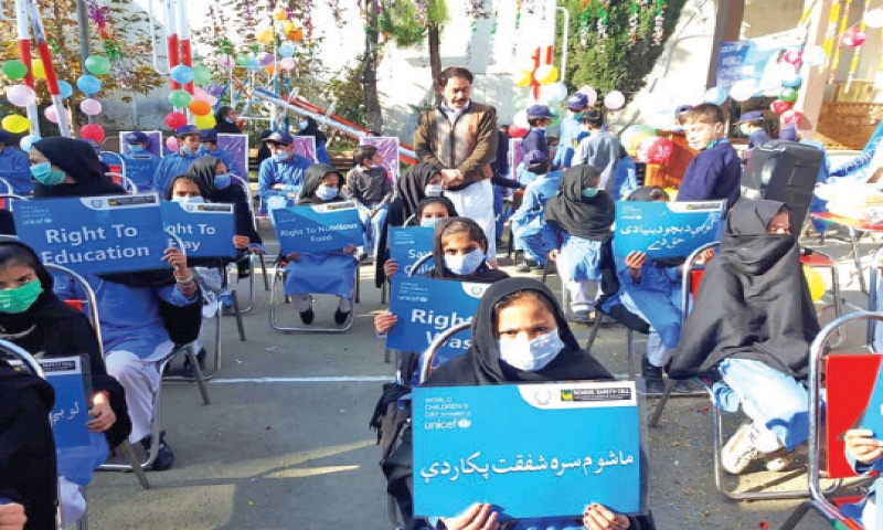 Students hold placards during a function held at a school in Lower Dir on Friday. — Dawn