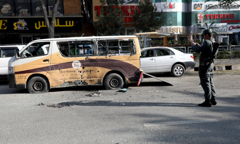 A police officer takes pictures of a damaged vehicle after rockets hit residential areas in Kabul, Afghanistan on Saturday. — Reuters