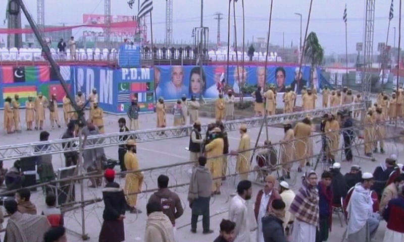 People stand near the stage set up for the Pakistan Democratic Movement's rally in Peshawar on Sunday. — DawnNewsTV