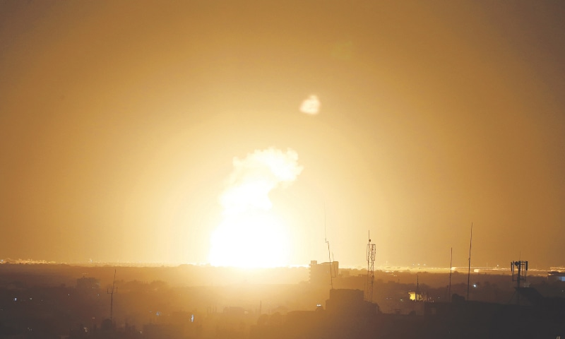 KHAN YUNIS: Flames follow after an Israeli air strike in the town of Khan Yunis, in the southern Gaza Strip, early on Sunday.—AFP
