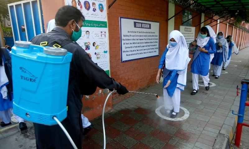 In this September 15 photo,  worker disinfects shoes of a student upon her arrival at a school in Lahore.  — AP