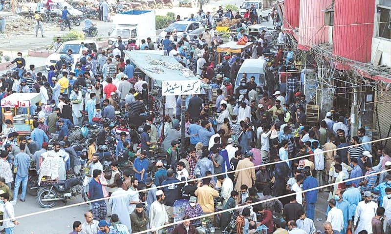 کراچی کے علاقے کریم آباد میں اتوار کے روز لوگوں کا ہجوم—تصویر: ڈان اخبار