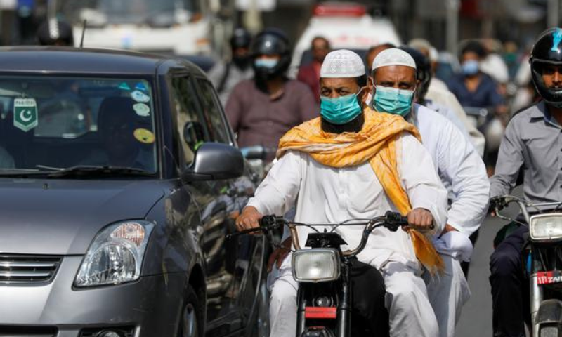Men wear protective masks as they ride a motorcycle amid the coronavirus outbreak in Karachi on Nov 16. — Reuters/File