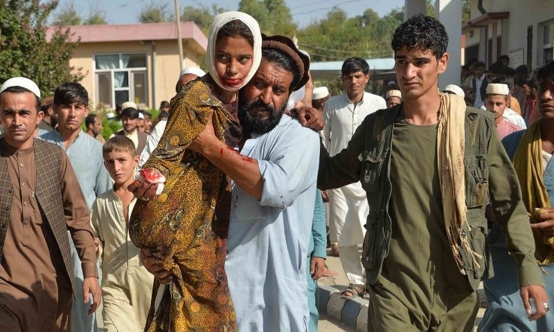 An injured youth (C-L) is carried to a hospital following a car bomb attack that targeted a government building, in the Ghani Khel district of Nangarhar province, on October 3. — AFP/File