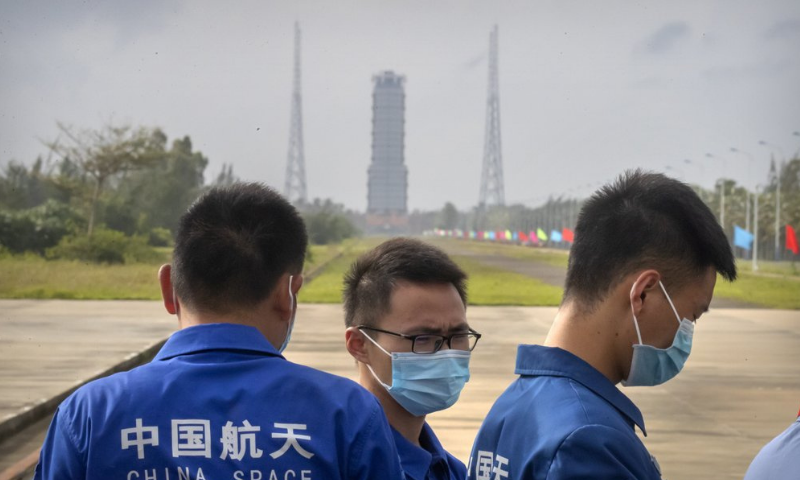 Workers wearing face masks stand near a launch pad at the Wenchang Space Launch Site in Wenchang in southern China's Hainan province on Monday. — AP