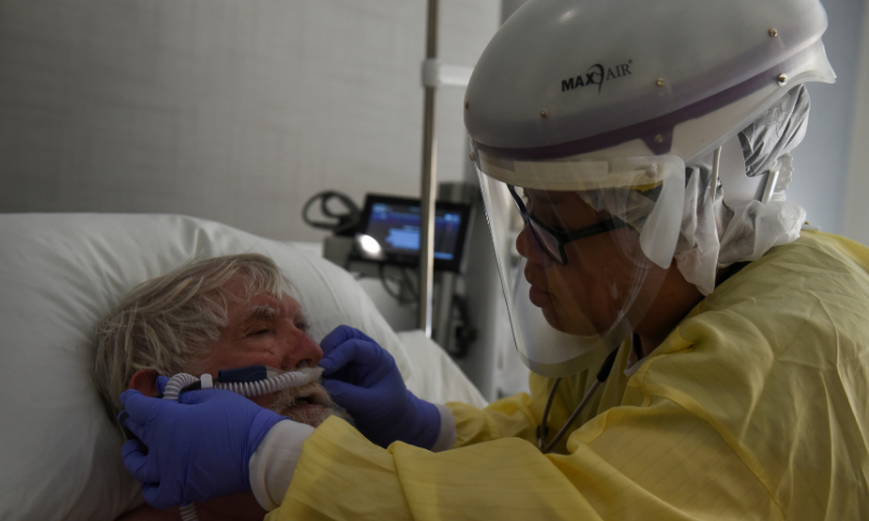 Teresa Ngyuen, a respiratory therapist, treats Lynn Stansel, a patient infected with Covid-19, at a hospital in Hutchinson, Kansas, US on November 20, 2020. — Reuters