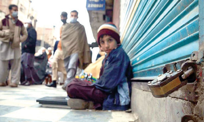 A boy sits outside one of the shops sealed in Qissa Khwani Bazaar, Peshawar, on Tuesday due to Covid-19 SOP violation. — APP