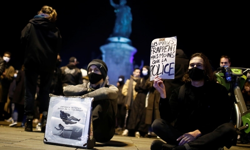 Demonstrators hold plackards during a protest to show support for asylum seekers in Paris on November 24. — Reuters