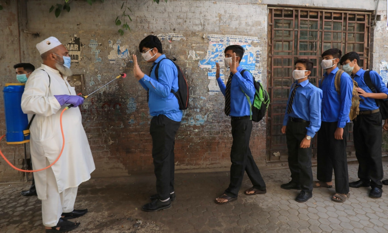 An employee disinfects students before they enter classes as schools reopen in Peshawar on September 15. — Reuters/File