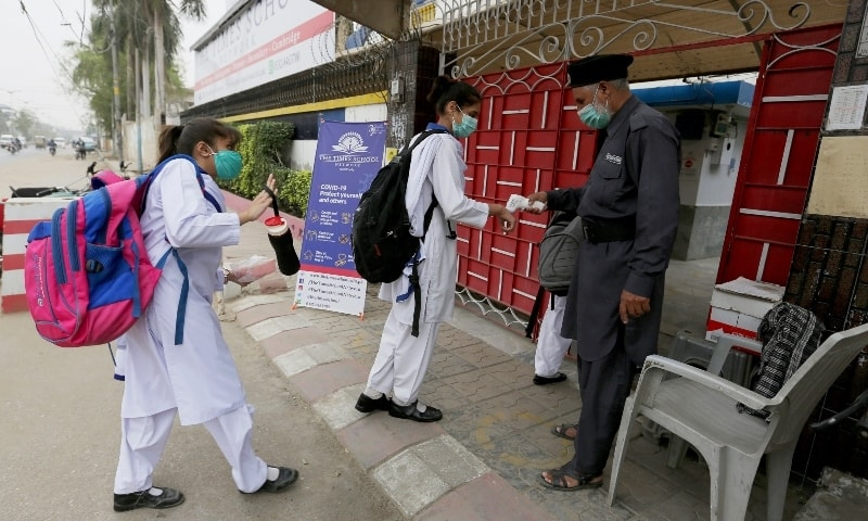 A worker checks body temperatures of students as they all wear face masks to protect against Covid-19 upon their arrival at a school in Karachi on November 24. — AP