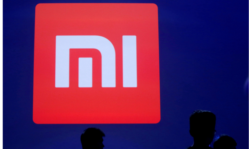 People are silhouetted in front of Xiaomi's logo at a venue in Beijing, May 10, 2016. — Reuters