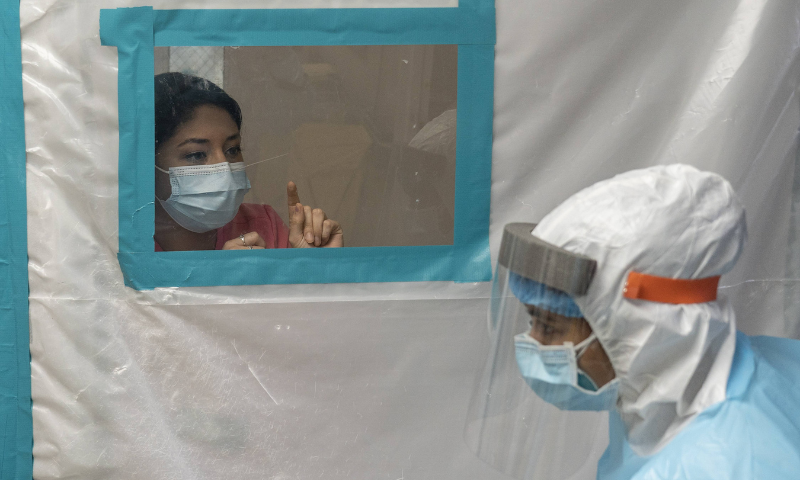 Medical staff members communicate with each other through a partition in the Covid-19 intensive care unit at the United Memorial Medical Center on November 25 in Houston, Texas. — AFP