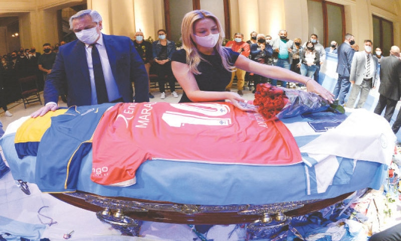 BUENOS AIRES: Argentina's first lady Fabiola Yanez places flowers on the casket of soccer legend Diego Maradona as Argentina's President Alberto Fernandez looks on, at the presidential palace Casa Rosada on Thursday.—Reuters
