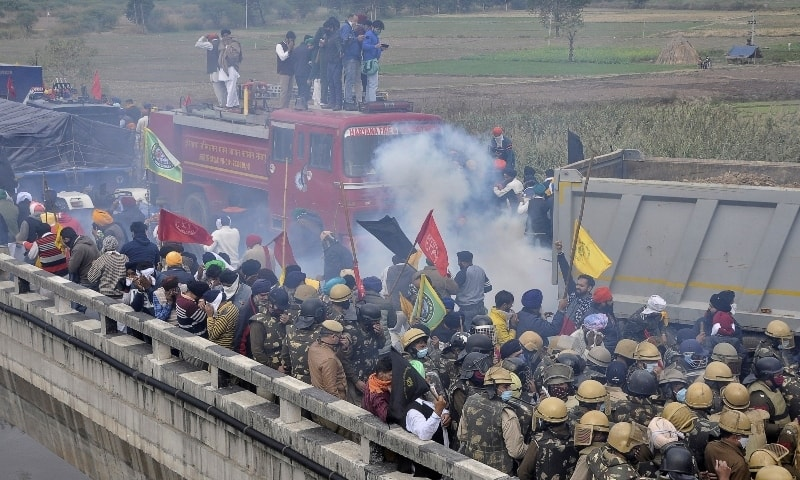 Farmers run away as police fire tear smoke shells to disperse the protesting farmers near Ambala on November 26. — Reuters
