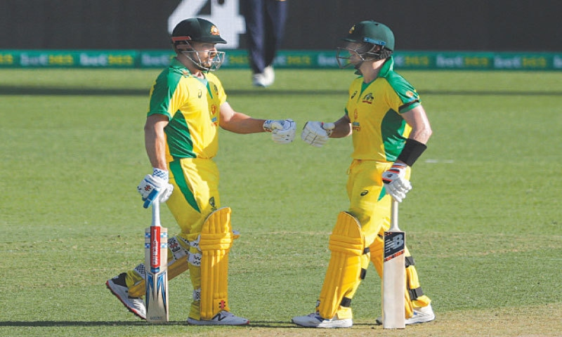 SYDNEY: Australian captain Aaron Finch (L) and fellow century-maker Steve Smith punch their gloves during the first One-day International against India at the Sydney Cricket Ground on Friday.—Reuters