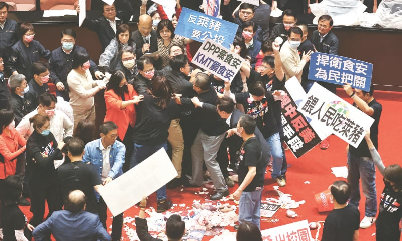 TAIPEI: Pork intestines and other parts are seen on the ground as lawmakers fight with each other in parliament on Friday.—Reuters