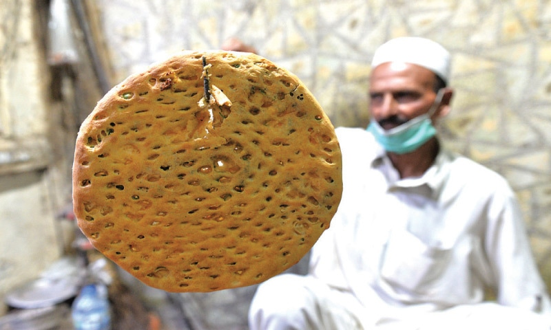 (Top and above) Aurangzaib pulls a naan out of the tandoor | Photos by Murtaza Ali