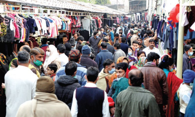 People crowd the weekly bazaar in Islamabad's Aabpara area on Sunday in total disregard to the health guidelines to protect against Covid-19. — Photo by Mohammad Asim