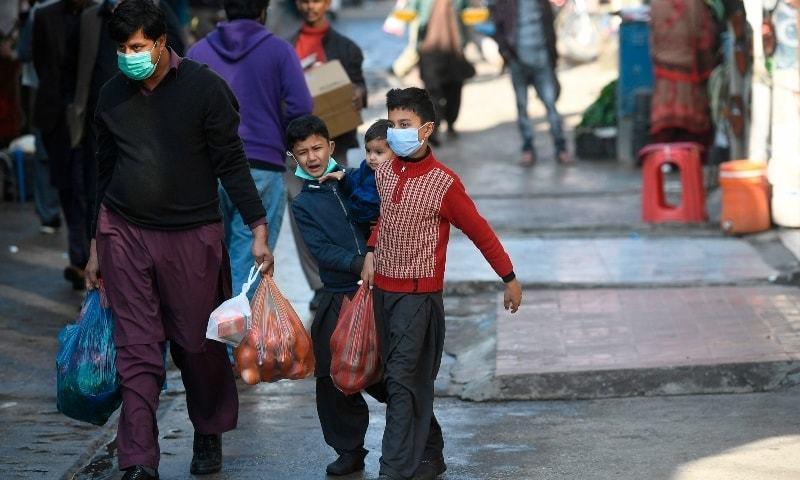 Shoppers wearing facemasks as a preventive measure against the coronavirus walk through a market in Islamabad on November 26. — AFP/File
