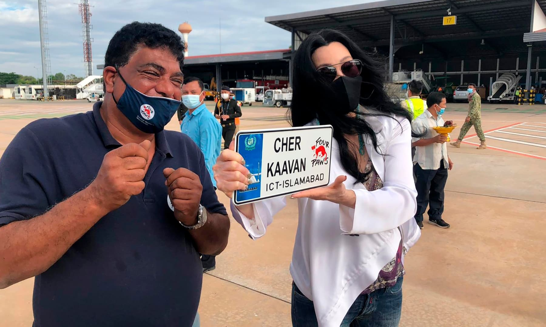 US singer and actress Cher, right, holds a vanity car plate while posing for a photograph with Dr Amir Khalil, a veterinarian from Four Paws upon arrival of Kaavan from Pakistan, at the Siem Reap International Airport, Cambodia, Monday. — AP