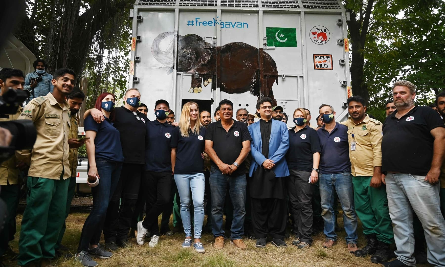 Officials of Four Paws International and wildlife rangers pose for a photograph beside a crate carrying Kaavan after placing it onto a trailer truck at the Marghazar Zoo in Islamabad on November 29. — AFP