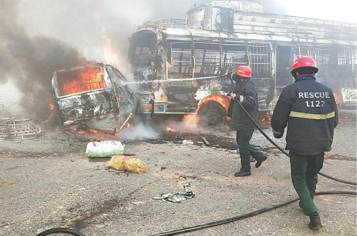SHEIKHUPURA: Firefighters extinguishing the fire after the collision between a van and a bus on Monday.