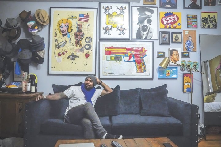 NEW YORK: Painter Guy Stanley Philoche, a 43-year-old Haitian immigrant and star in the New York art world, surrounded with works collected from other artists.—AP