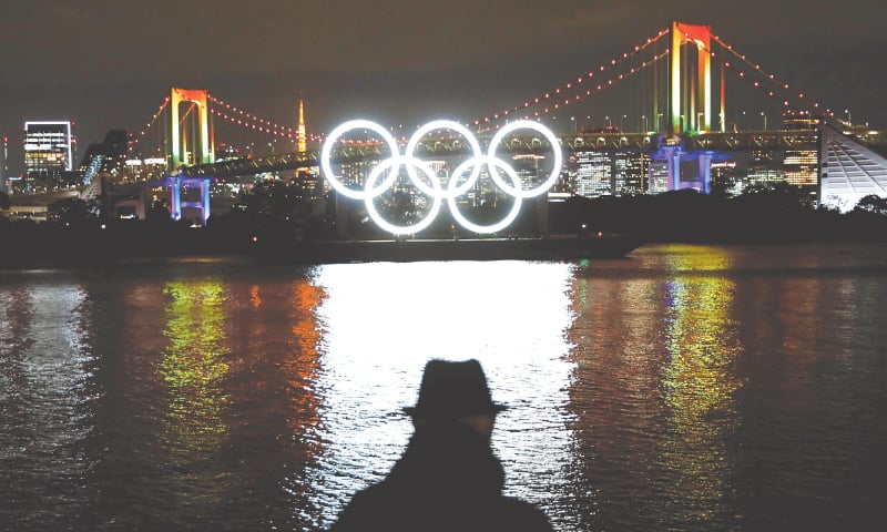 TOKYO: The giant Olympic rings which were temporarily taken down in August for maintenance are illuminated after being reinstalled at the waterfront area at Odaiba Marine Park.—Reuters