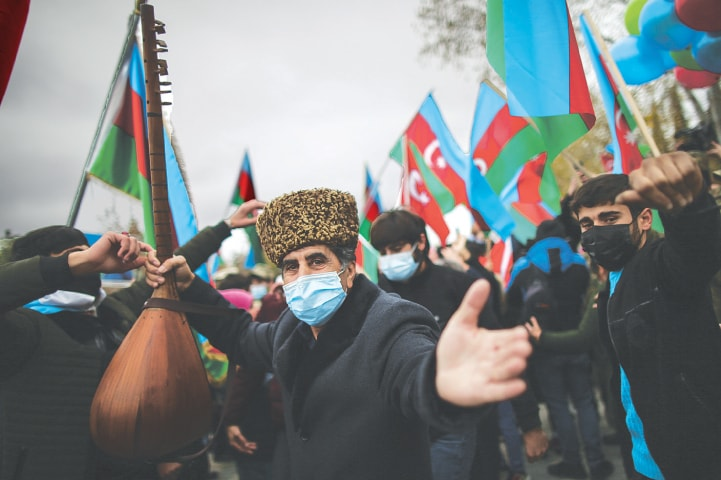 AGHJABADI (Azerbaijan): An Azerbaijani man dances and other people hold aloft national flags as they celebrate the transfer of Lachin region to Azerbaijan's control on Tuesday as part of a peace deal that required Armenian forces to cede Azerbaijani territories they held outside Nagorno-Karabakh.—AP