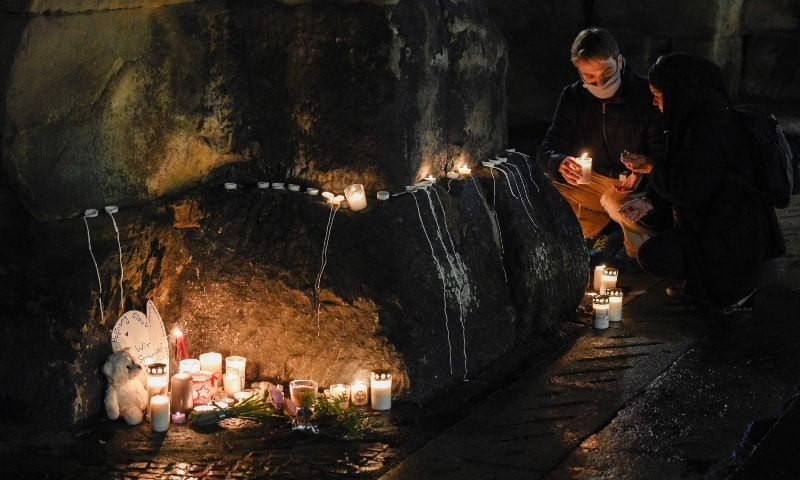 People light candles at the landmark monument, the Porta Nigra, for the victims after a car drove into pedestrians in Trier, southwestern Germany, on December 1. — AFP