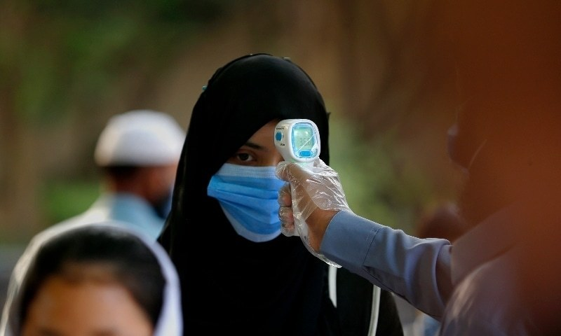 A worker checks body temperature of student at a school in Islamabad on September 15. — AP/File