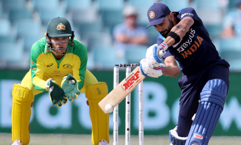 India's captain Virat Kohli plays a shot as Australia's wicketkeeper Alex Carey (L) looks on during the third one-day international cricket match between Australia and India at Manuka Oval in Canberra on December 2, 2020.— AP
