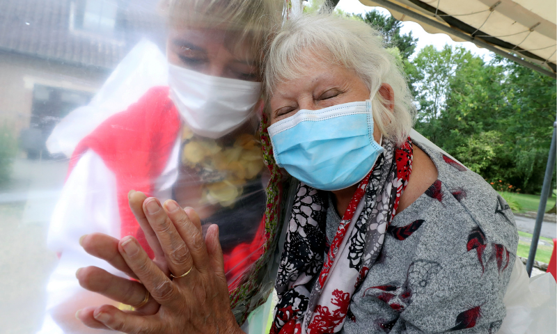 "Lily Hendrickx, 83, a resident at Belgian nursing home ""Le Jardin de Picardie"" enjoys hugs and cuddles with Marie-Christine Desoer, the director of the residence, through a wall made with plastic sheets to protect against potential coronavirus infection, in Peruwelz, Belgium on July 1, 2020. — Reuters"