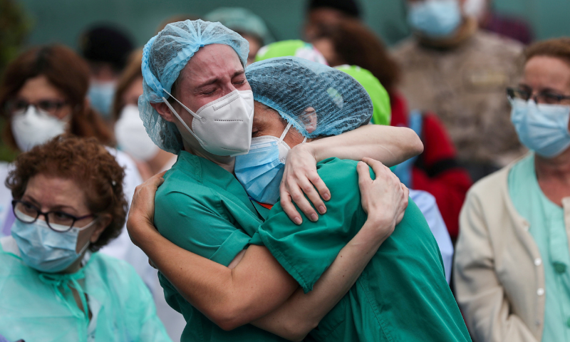 Health workers wearing protective face masks react during a tribute for their co-worker Esteban, a male nurse that died of complications related to Covid-19 outside the Severo Ochoa Hospital in Leganes, Spain on April 13, 2020. — Reuters