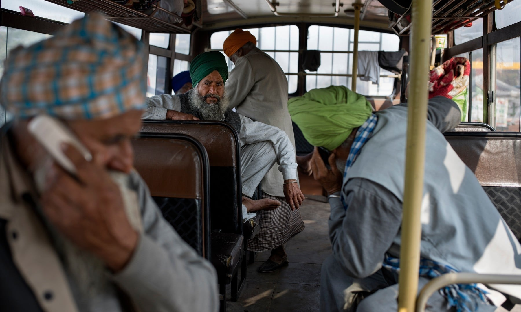 Protesting farmers speak on their mobile phones as they sit inside a school bus in which they traveled to a protest site, at the Delhi-Haryana state border on Dec 1. — AP