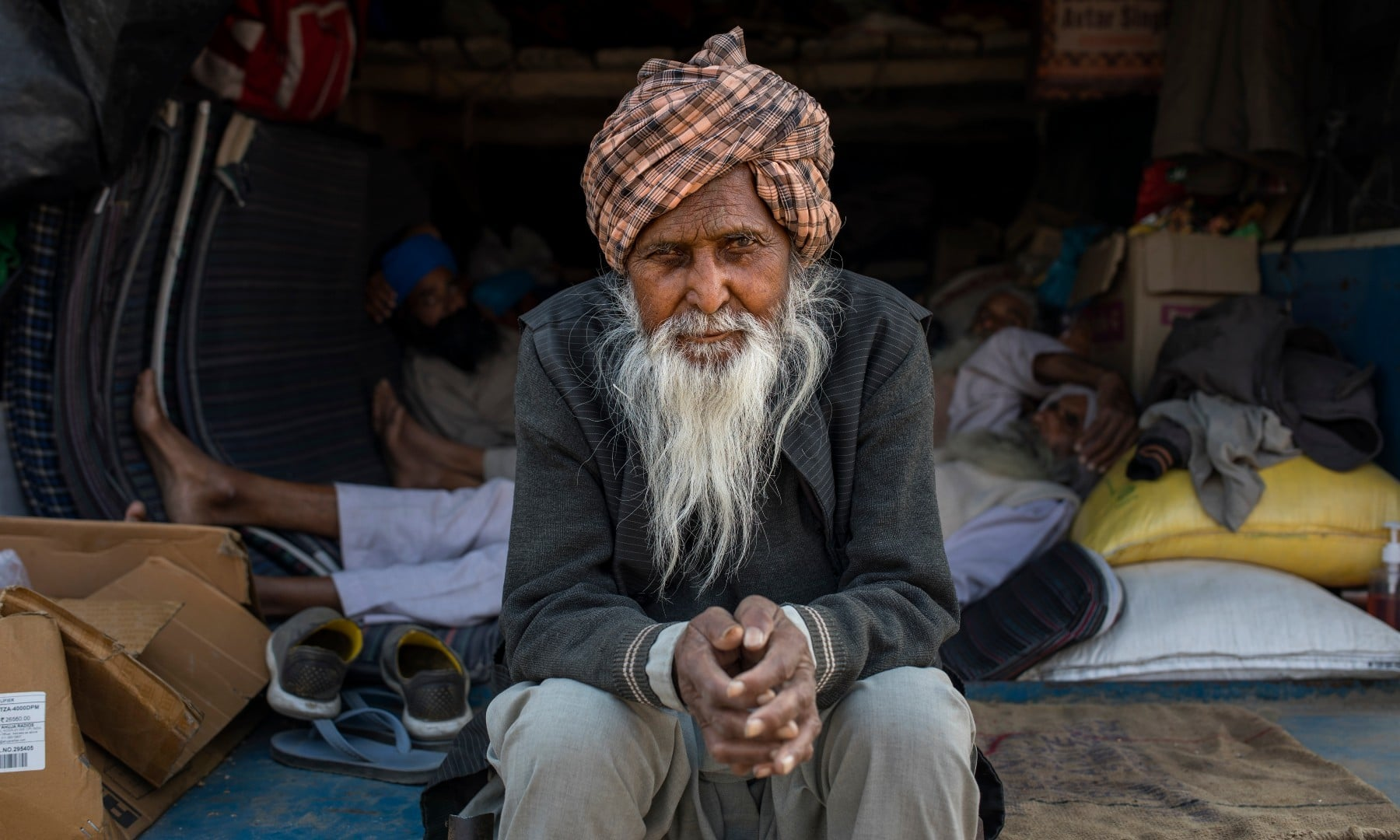 Amrik Singh Mikka, 78, sits for a photograph on the back of his tractor trailer parked on a highway during a protest against new farm bills at the Delhi-Haryana state border on Dec 1. — AP