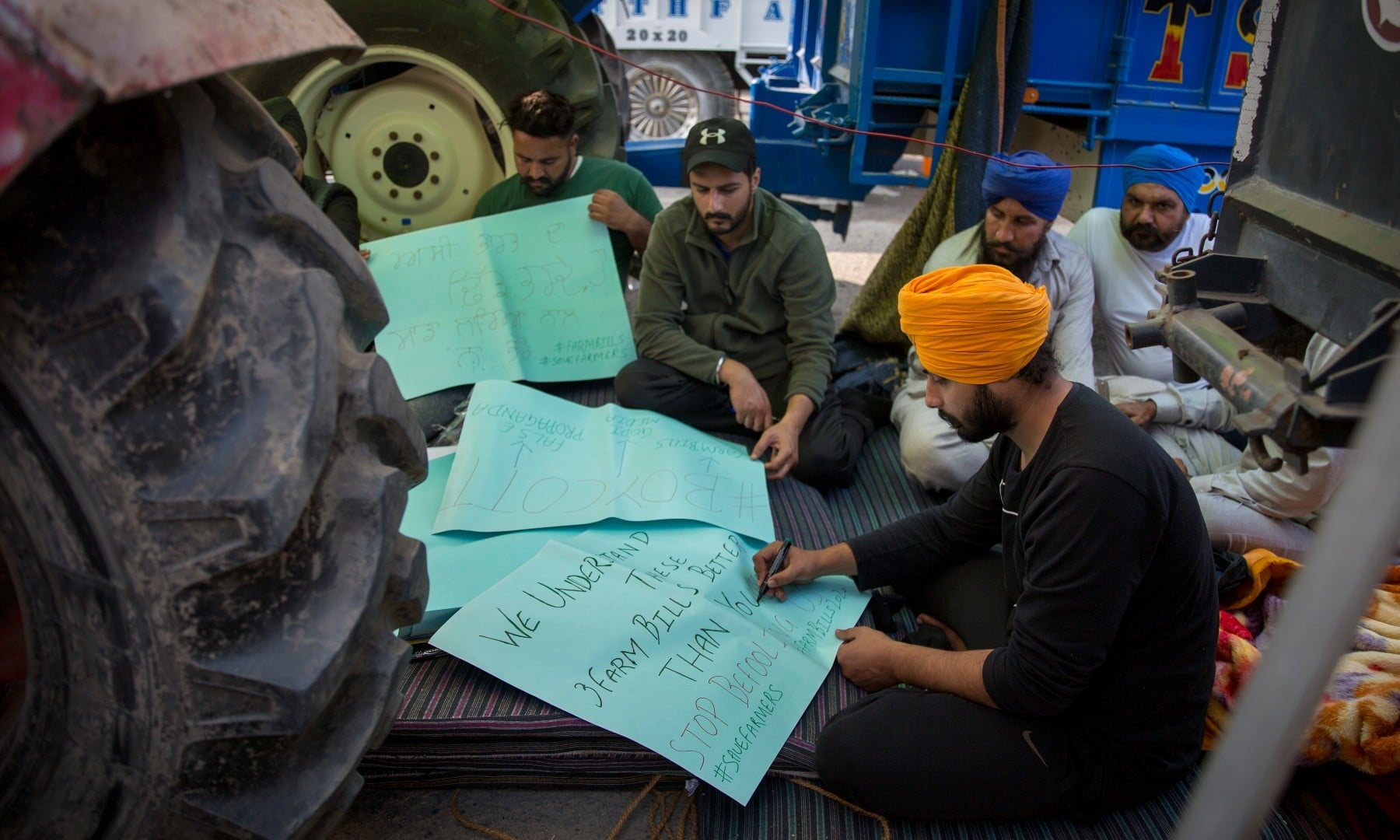 Young farmers make placards as they block a major highway during a protest against new farming laws at the Delhi-Haryana state border on Dec 1. — AP