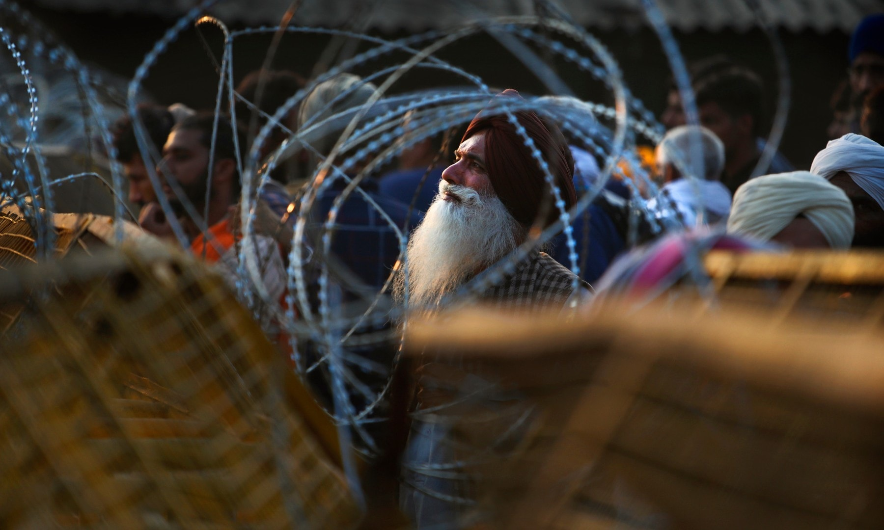 An Indian farmer looks through the barbed wires put up by the police at the site of a protest on a highway at the Delhi-Haryana state border on Dec 3. — AP