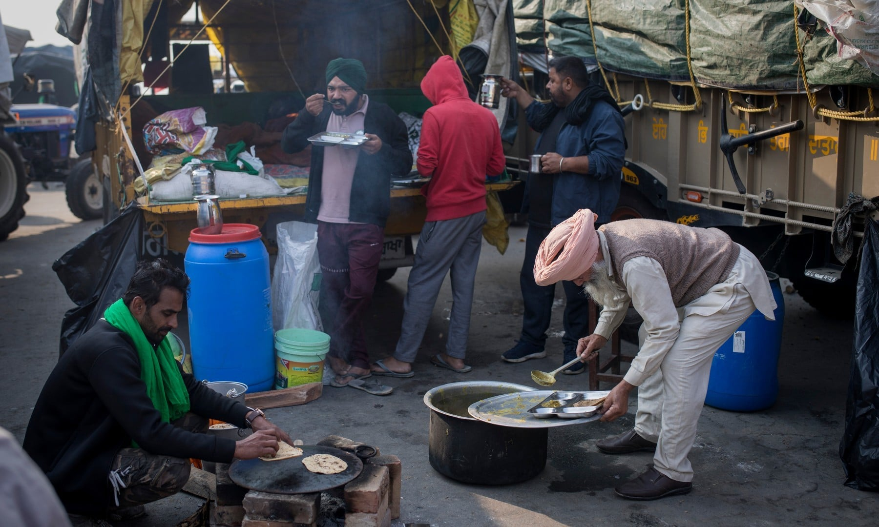 Protesting farmers eat breakfast outside their vehicles as they block a major highway during a protest at the Delhi-Haryana state border on Dec 1. — AP