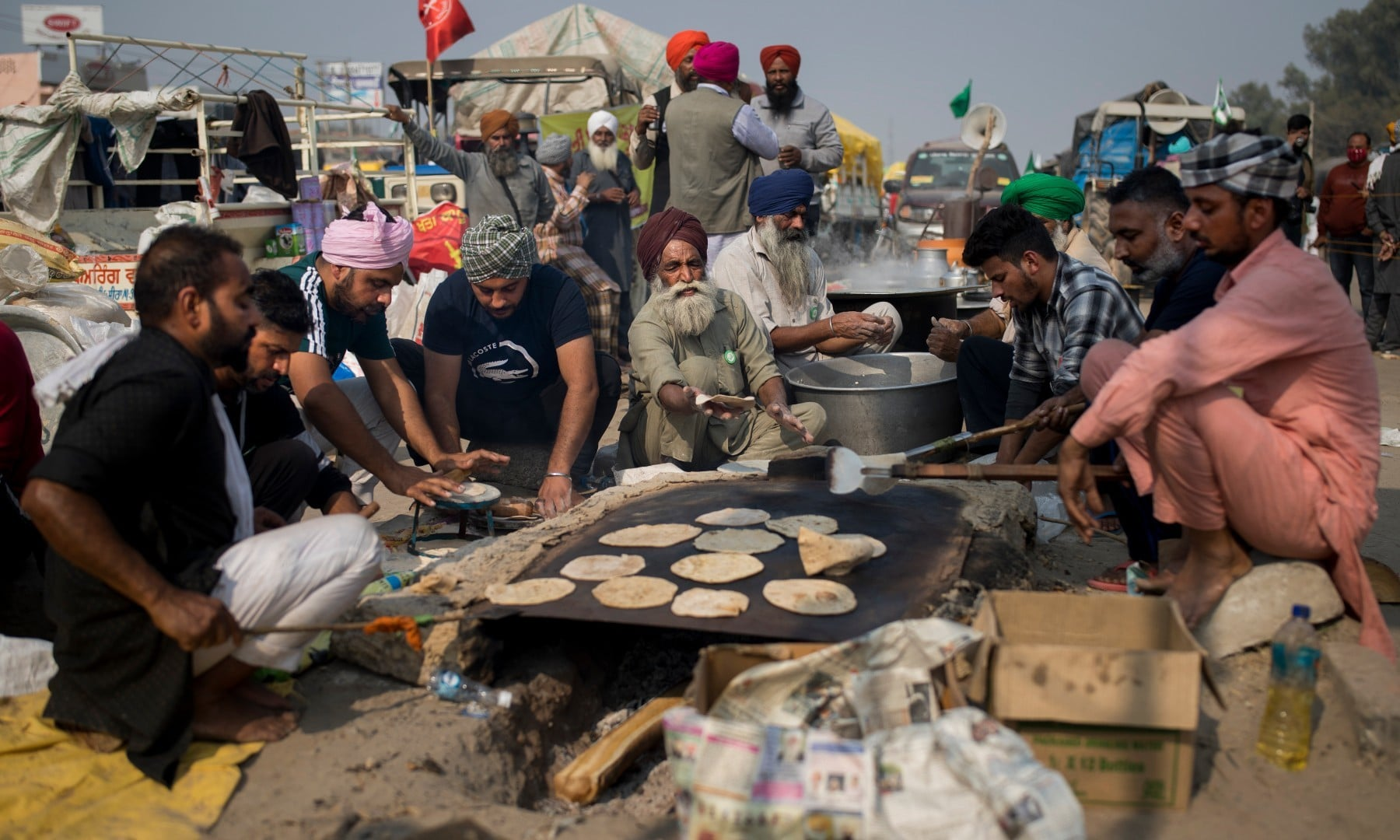 Protesting farmers prepare flat bread for fellow farmers as they block a major highway during a protest against new farming laws at the Delhi-Haryana state border on Dec 1. — AP
