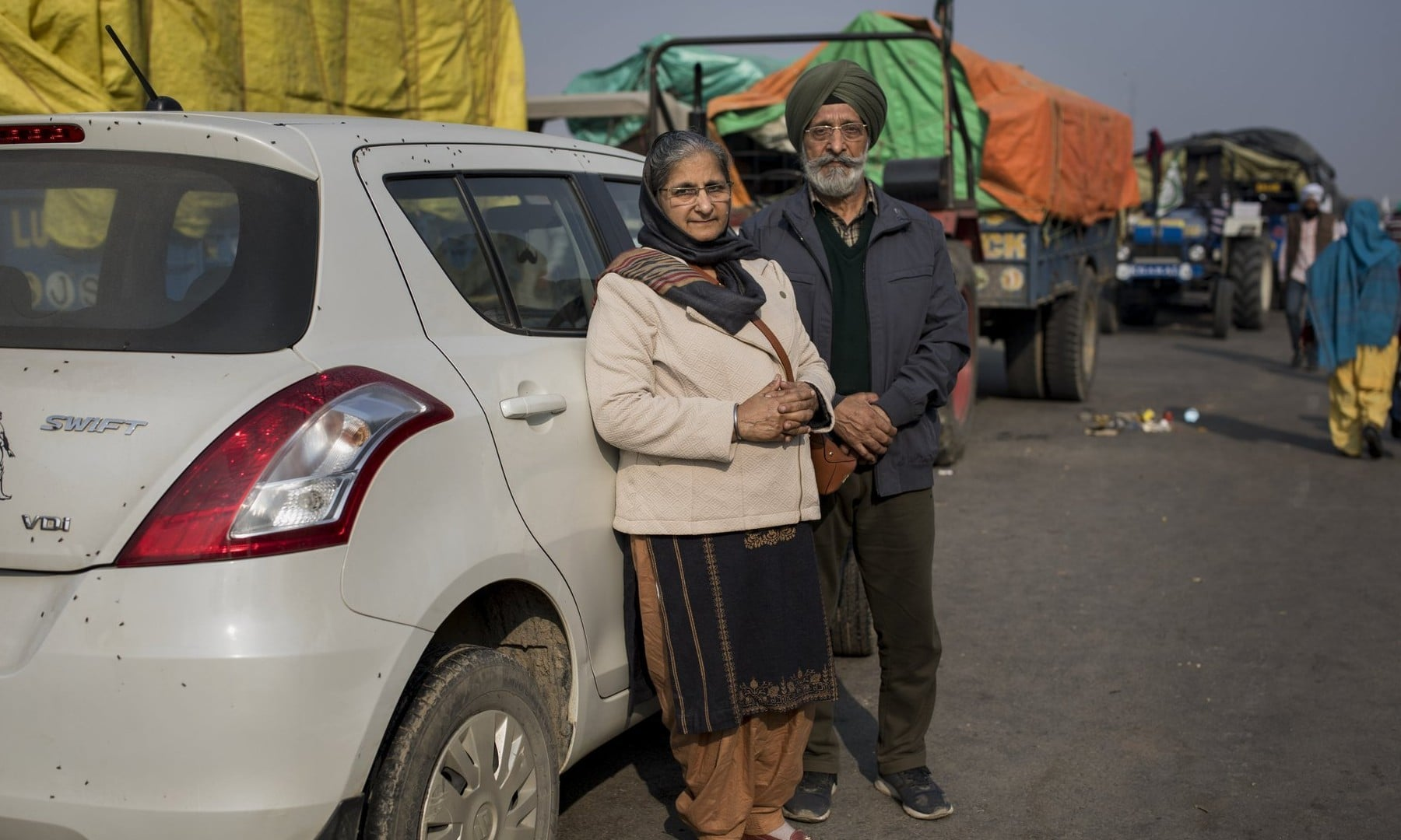 Dharam Singh Sandhu, 67, and his wife Nirmaljeet Singh Kaur, 66, stand for a photograph next to their car where they are spending nights parked near the site of a protest against new farming laws, at the Delhi-Haryana state border on Dec 1. —  AP