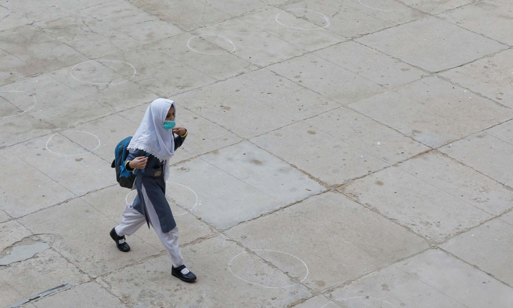 A student wearing protective mask walks over the marks for safe distancing as schools reopen in Karachi on September 15. — Reuters